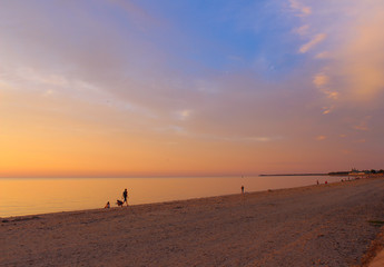 A beautiful sunset on the beach on a calm summer evening, the smooth surface of the windless sea reflects the delightful colors of the sky as a big mirror.