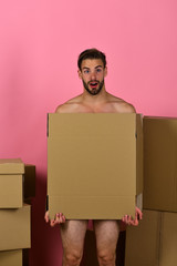 Macho with beard and surprised face covering himself with box