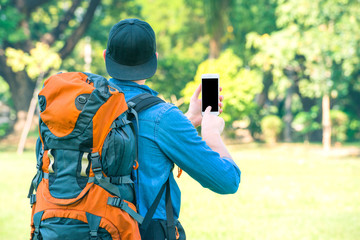 Tourist man with a backpack holding a phone in the nature. Digital nomad and travel tourism hike technology concept