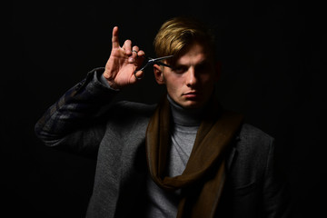 Stylist in suit and scarf on black background.