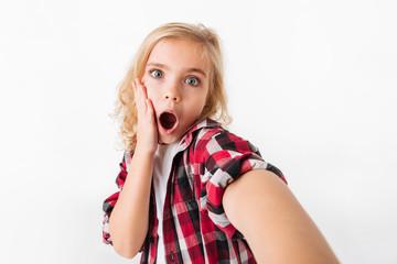 Portrait of a surprised little girl taking a selfie