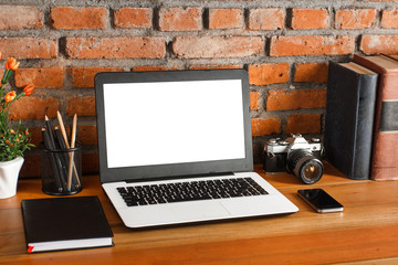 working space on wooden table and brick wall background