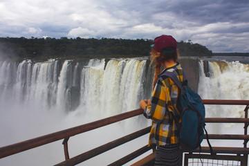 young caucasian woman looking at Iguazu Falls, Brazil