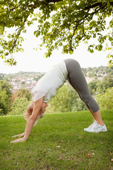 Mature woman doing yoga stretch in park