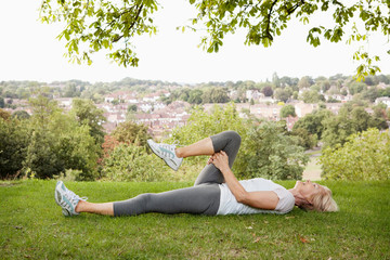 Mature woman stretches leg in park