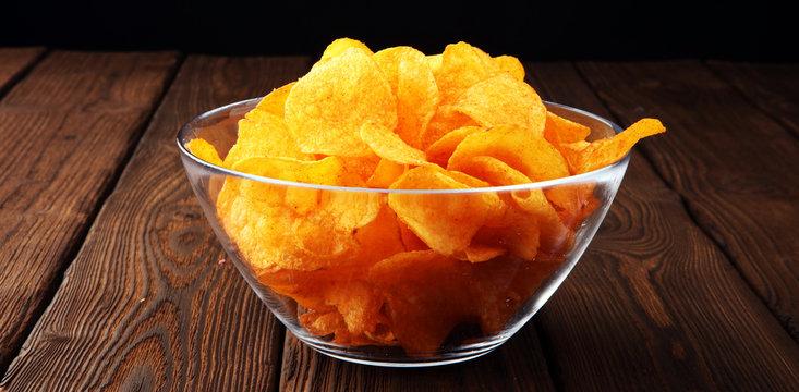 Crispy potato chips. Paprika chips on wooden background.