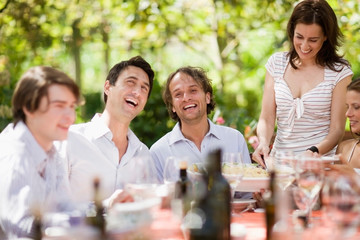 Laughing people sitting on a table