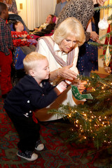 Britain's Camilla, Duchess of Cornwall is seen with a child from Helen & Douglas House and Roald Dhal's Marvellous Children's Charity decorating the Clarence House Christmas tree at Clarence House  in London