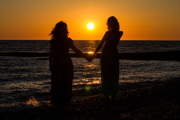 2 girls stand holding hands on the ocean shore