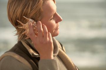 Woman by sea, listening in seashell
