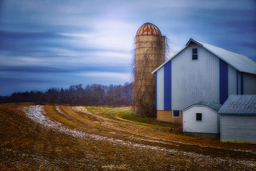 A quiet midwestern farmstead in winter, with glowing sky, silo and blue and white barn