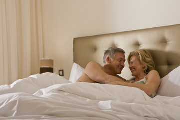 Mature couple embracing tenderly in bed