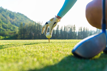 hand of woman golf player gentle put a golf ball onto wooden tee on the tee off, to make ready hit away from tee off to the fairway ahead.