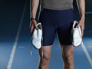 Man carrying running shoes on track