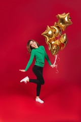 Happy young pretty woman holding balloons.