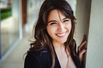 Portrait of a beautiful brunette laughing by the wall