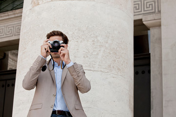 Man taking pictures by columned building