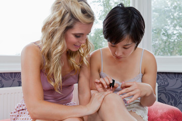 Women painting each other's nails