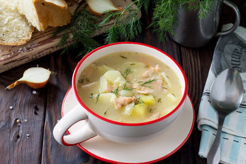 Finnish fish soup with salmon on a kitchen wooden kitchen table.