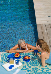 Woman in swimming pool talking to woman