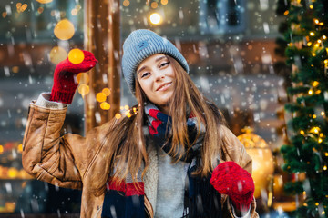 Beautiful smiling woman with garland walking at the city street. Attractive girl dressed in warm hat, scarf and red mittens. Magic snowfall effect.
