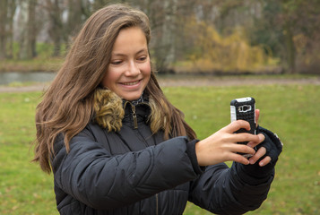 girl takes pictures with her mobile phone in park