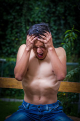 Close up of shirtless man suffering from anorexy, screaming with both arms around her head suffering pain, in a blurred background