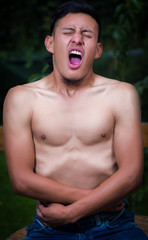 Close up of shirtless lonely man suffering of anorexy, screaming and holding his stomach with both hands, in a blurred background