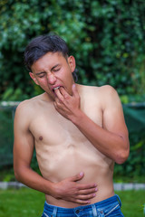 Close up of shirtless lonely man suffering of anorexy, putting his fingers in his mouth to induce to vomit, in a blurred nature background