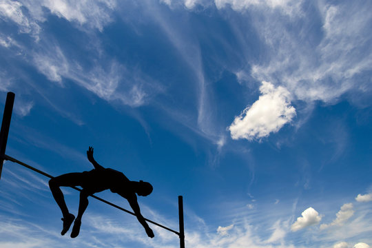 Silhouette of athlete competing in pole vault under the blue sky