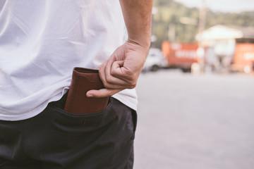 Rear view of man keeping wallet in back pocket of his chino pant