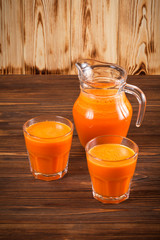 Pumpkin fresh juice in beautiful glasses and jug with pieces of ripe vegetable on brown wooden background. Sweet orange juice. Healthy eating, diet theme. Close up photography. Vertical banner