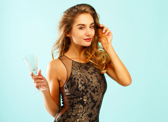 Young beautiful woman with a glass of champagne over blue background