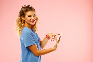 Portrait of a beautiful young woman with tablet over pink background