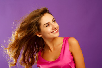 Beautiful young woman posing in studio over violet background. Fashion concept.