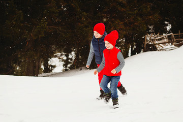 Young two happy kids playing outdoors in winter park