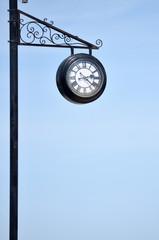 Clock on an iron pillar against a blue sky.