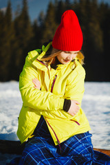 Young happy woman sitting on the top of mountain in snowy winter