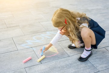 Mothers Day. Child girl draws gift surprise to Mummy - picture of crayons on the asphalt. Background gray surface of tiles on the outdoor