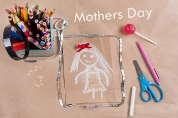 Child's drawing of mother. Mothers Day. Background of old kraft paper, colored pencil, candy on a stick.