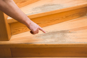Keuken foto achterwand Trappen Man's hand pointing to the old scratched wooden stairs' step in the house. Problems and solutions concept.