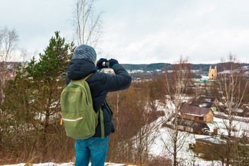 A teenager boy travels and takes off everything seen on the action camera. Winter village is on the background.