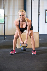 Determined Female Athlete Exercising With Kettlebell In Warehous