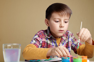 Caucasian boy is painting with watercolors.