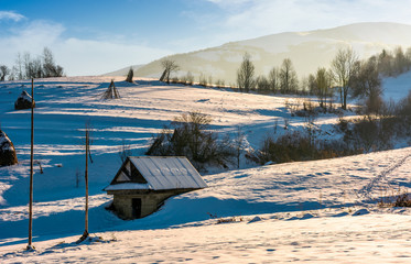shed on snow covered agricultural hillside. lovely rural scenery in winter