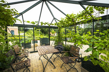 Terrace in a glass house with wooden garden furniture