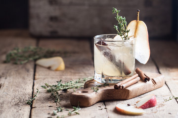 Cold pear white tea with thyme, cinna mon and honey on the olive desk and wooden background