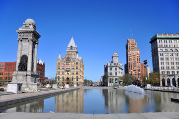 Soldiers' and Sailors' Monument and Syracuse Saving Bank Building at Clinton Square in downtown Syracuse, New York State, USA. Syracuse Savings Bank Building was built in 1876 with Gothic style.