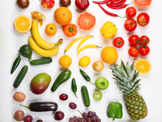 Creative composition made of fruits and vegetables in rainbow colors on white background, flat lay