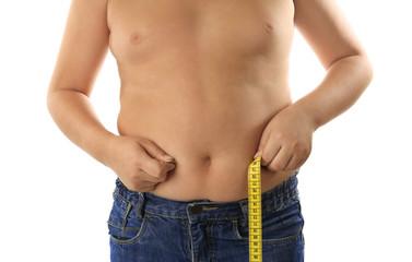 Overweight boy measuring waist on white background, closeup